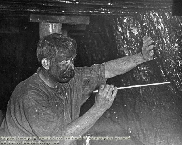 Miner with face blackened by coal dust
